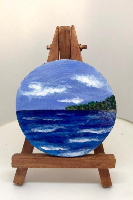 Mini painting of blue sky and sea on wood slice with easel